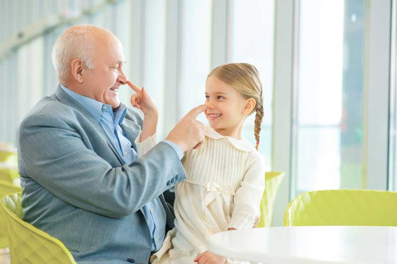 Older Man Playing and Laughing with Child - ChangingAging