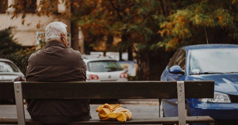 Older man sitting on a bench near a parking lot - ChangingAging.org